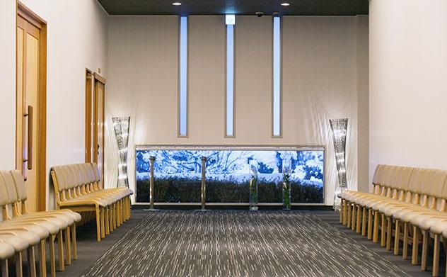 メモリアルホールみつわ式場前のロビー、椅子が整列した広い空間に豪華なライティングのオブジェ
