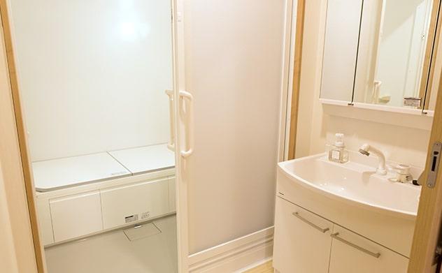 洗面所と大きめの浴槽を備えたバスルーム
