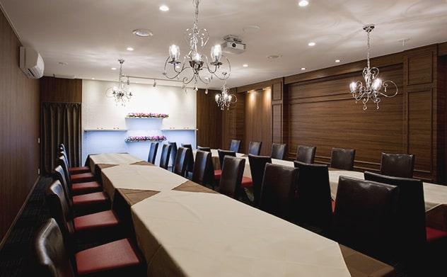 おしゃれな会食会場全体、綺麗なシャンデリアと皮の椅子、長テーブル