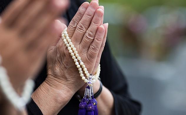 数珠をつけて両手を合わせる女性の手元
