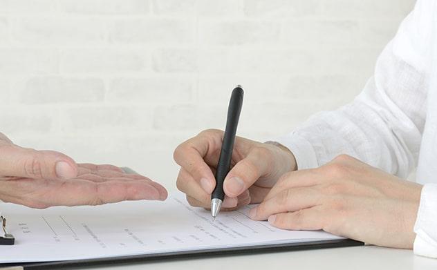 手続き書類にkにゅうする方法を教えてもらっている男性の手元