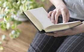相続について本を読んで調べる女性の手元